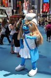 NYC: Smurfette in Times Square. An actor dressed as the loveable Smurfette TV character welcomes guests to NYC's Times Square with a wave and an offer to pose stock images
