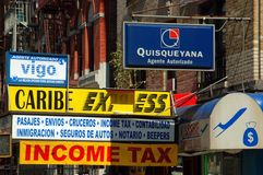 NYC: Spanish Harlem Business Signs. Colourful multi-lingual signs in both English and Spanish outside a business offer aid for taxes, immigration, a notary Royalty Free Stock Image