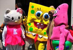 NYC: Sponge Bob and Friends in Times Square. New York City: Sponge Bob, Hello Kitty, and Pink pose with a tourist in Times Square royalty free stock photos
