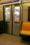 NYC Subway Doors. Shot from inside a New York City subway car of the windows on the doors tagged with graffiti, orange seat next to doors royalty free stock photo