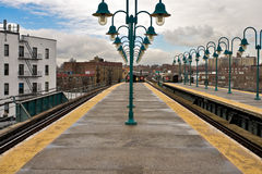NYC subway platform looking at arriving train. Empty cloudy buildings stock photo