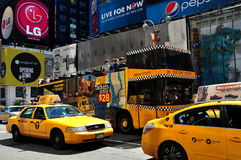 NYC: Taxis and Tour Bus in Times Square. Yellow medallion taxi cabs and a double decker Big Taxi Tour bus in the heart of NYC's Times Square royalty free stock photography