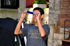 NYC: Teenaged boy with toy telescope. A teenaged boy tries out a toy telescope at the West 75th Street Block Association's annual street festival / yard sale in Royalty Free Stock Photos