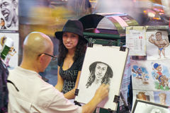NYC, Times Square Artists. NEW YORK - SEPTEMBER 4: Unknown street artist drawing portraits and exhibiting works in Times Square by night on September 04, 2011 in royalty free stock photo