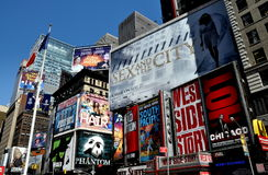 NYC: Times Square Billboards. Huge advertising billboards cover the sides of buildings promoting Broadway musicals and films in Times Square at West 46th Street royalty free stock images