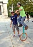 NYC: Trainer, der Unicycle-Mitfahrer hilft Lizenzfreies Stockfoto