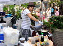 NYC: Uomo che cucina alimento tailandese Fotografia Stock