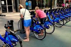 NYC: Vrouw die Citibikes gebruiken bij het Dokken van Post Stock Foto
