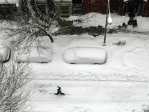 NYC: Winter Snowstorm. A lone skier makes his way up West 82nd Street in New York City following a winter blizzard which has buried nearby cars under a blanket Royalty Free Stock Photo