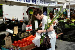 NYC: Woman at Farmer's Market. A woman holding a bunch of Gladiolas shopping for farm fresh tomatoes at the Lincoln Square Farmer's Market on Manhattan's Upper Stock Photos