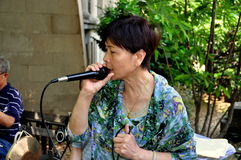 NYC: Woman Singing Chinese Songs in Chinatown Park Royalty Free Stock Images