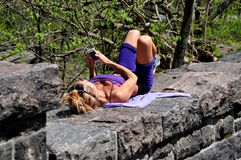 NYC: Woman Sunbathing using Cellphone Stock Images