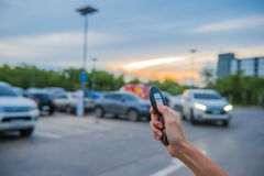Nyckel- bil för fjärrkontroll i hand i den utomhus- parkeringsplatsen på aftonen Royaltyfri Bild