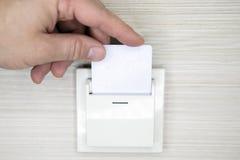 Nyckel- kort för Closeuphandmellanlägg till öppnande ljus som är elektroniskt i hotellrum arkivfoto