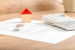 Nyckel- ligga för silverhus på ett avtal för husförsäljning Royaltyfri Fotografi