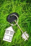Nyckel- och grönt gräs för hus Arkivbild