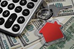 Nyckel- räknemaskin, pengar och hus Arkivfoto