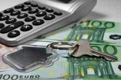 Nyckel- räknemaskin, pengar och hus Royaltyfri Bild