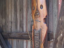 Nyckelharpa. An old swedish instrument used to play folk music hanging on an old barn wall Stock Photos