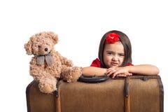 Nyckfull liten flicka med resväska- och leksakbjörnen arkivbilder