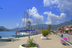 Nydri embankment,Lefkada,Greece. Anchored sailing boats at Nydri Marina and town promenade ,Lefkada,Greece Stock Photography