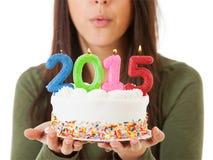 NYE :吹灭在2015生日蛋糕的妇女蜡烛 免版税库存照片