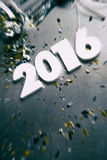 NYE: Enfoque del año 2016 en medio del confeti del partido Imágenes de archivo libres de regalías