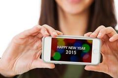 NYE: Frau, die Handy mit guten Rutsch ins Neue Jahr-Mitteilung hält Stockbild