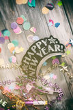 NYE: Fun Party Favors On Confetti And Wooden Background Royalty Free Stock Photography