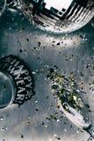 NYE: Fundo do metal do disco com confetes derramados do vidro Imagem de Stock Royalty Free