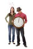 NYE : La femme jette des confettis pendant que l'horloge heurte le minuit Image stock