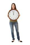 NYE: Mujer que sostiene el reloj por tiempo cerca de la medianoche Imagen de archivo