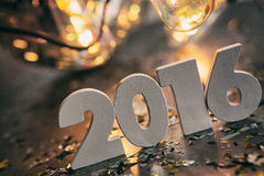 NYE: Números pelo ano novo 2016 com bulbos e confetes antigos Fotografia de Stock Royalty Free
