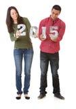 NYE: Pares jovenes que llevan a cabo los números por el Año Nuevo 2015 Imágenes de archivo libres de regalías
