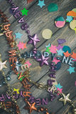NYE: Party Confetti and Happy New Year Necklaces On Wooden Backg Stock Photography