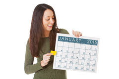 NYE: Woman Starting To Make Appointments In January 2015. Series with a young man and woman celebrating New Year's Eve, some with 2015 as the subject, isolated Royalty Free Stock Photos