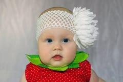 Nyfödd flicka med den stora pilbågen för vit blomma Arkivbild