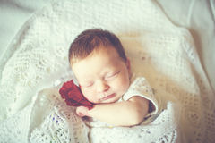 Nyfödd flicka som sover i en filt Arkivfoto
