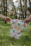 Nyfödd kläder i förälderhänder Arkivfoto