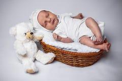 Nyfödd pojke som ligger i en korg royaltyfri foto