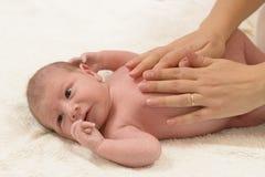 Nyfödda Baby som får olje- massage Arkivbilder
