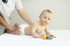 Nyfödda Baby som får olje- massage royaltyfria bilder