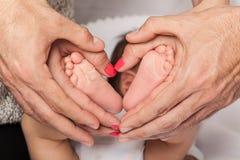 Nyfödda babys fot i händerna av mamman och farsan som bildar en hjärta Arkivfoto