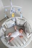 Nyfödda lögner i den runda vita sängen med mobilen Royaltyfri Foto