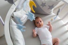 Nyfödda lögner i den runda vita sängen med mobilen Royaltyfria Foton