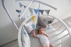 Nyfödda lögner i den runda vita sängen med mobilen Royaltyfri Fotografi