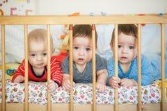 Nyfödda trillingar ligger i sängen Royaltyfri Foto