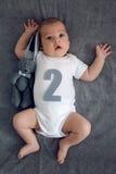 Nyfödda två månader som ligger på sängen med en leksak, oavbrutet tjata Fotografering för Bildbyråer