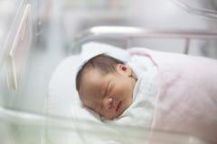 Nyfött begynna sovande i filten i leveransrum Arkivbilder