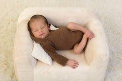 Nyfött behandla som ett barn att koppla av i fåtölj royaltyfria bilder